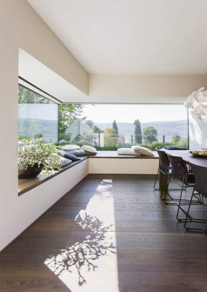 Angular bay window in a modern living room, a great biophilic design example.