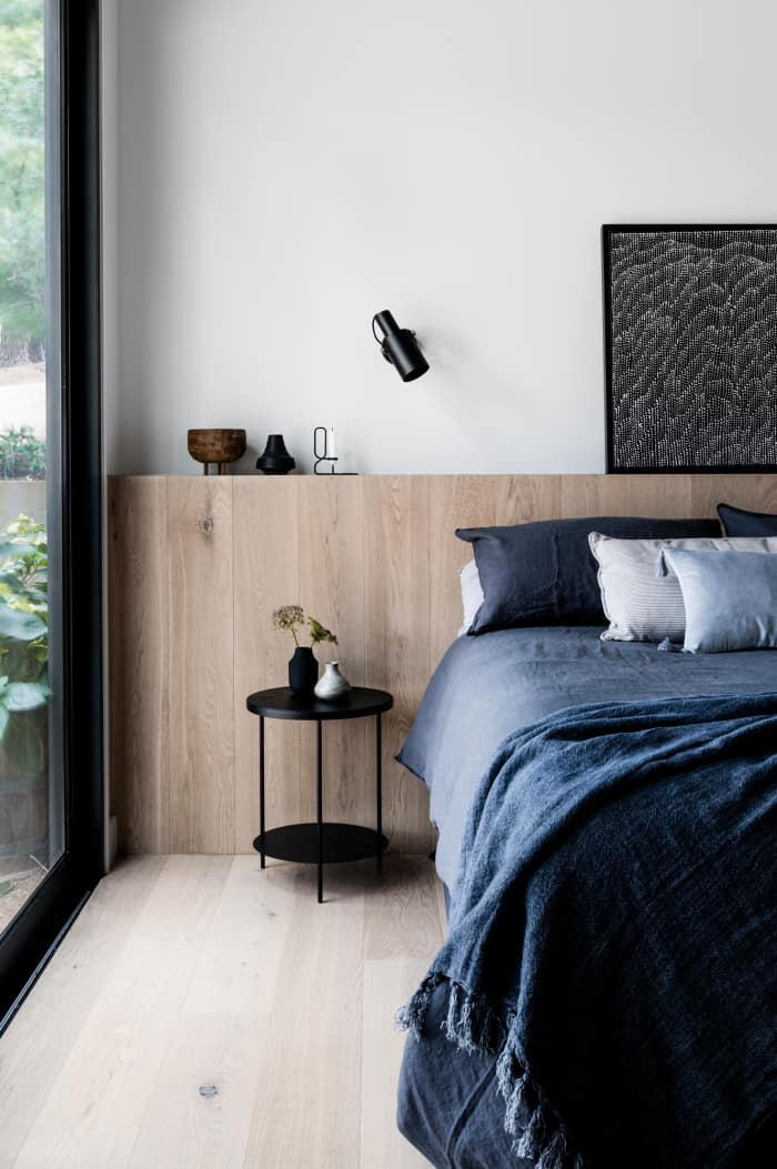 Minimalist bedroom with big window, great example of biophilic design.