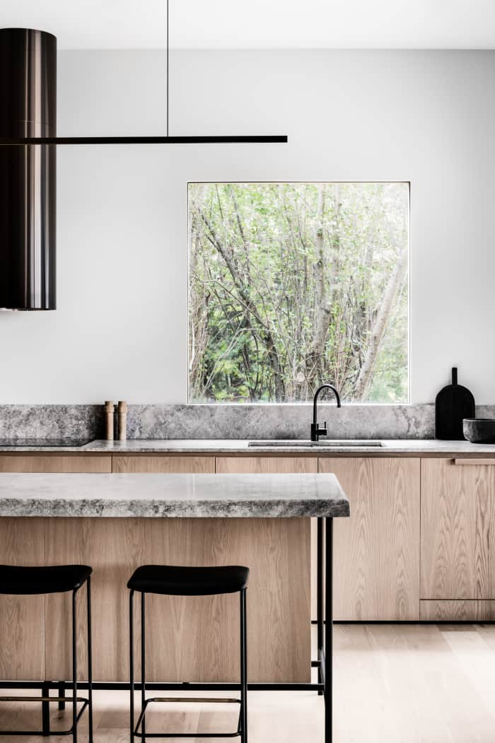 Minimalist kitchen with wood cabinets and stone countertops, great example of biophilic design.