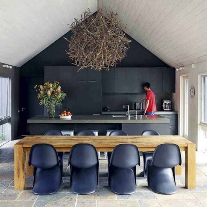 Black mat Panton chairs and a black modern open kitchen. A massive wood table and a rustic wooden chandelier create a blend of modern and rustic in the space.