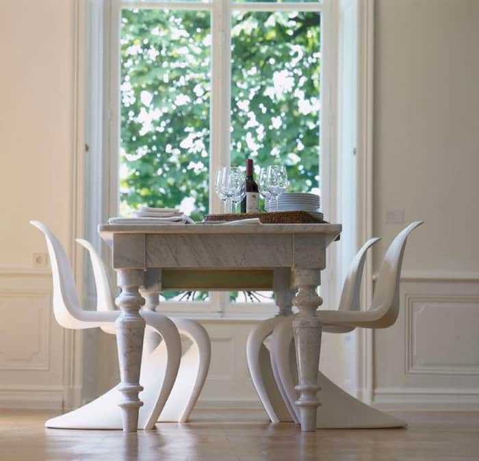 White Panton chairs around a classic marble table.