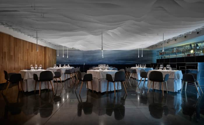 Restaurant with wavy-shaped panels dropping from the ceiling, creating an overall ethereal feel.
