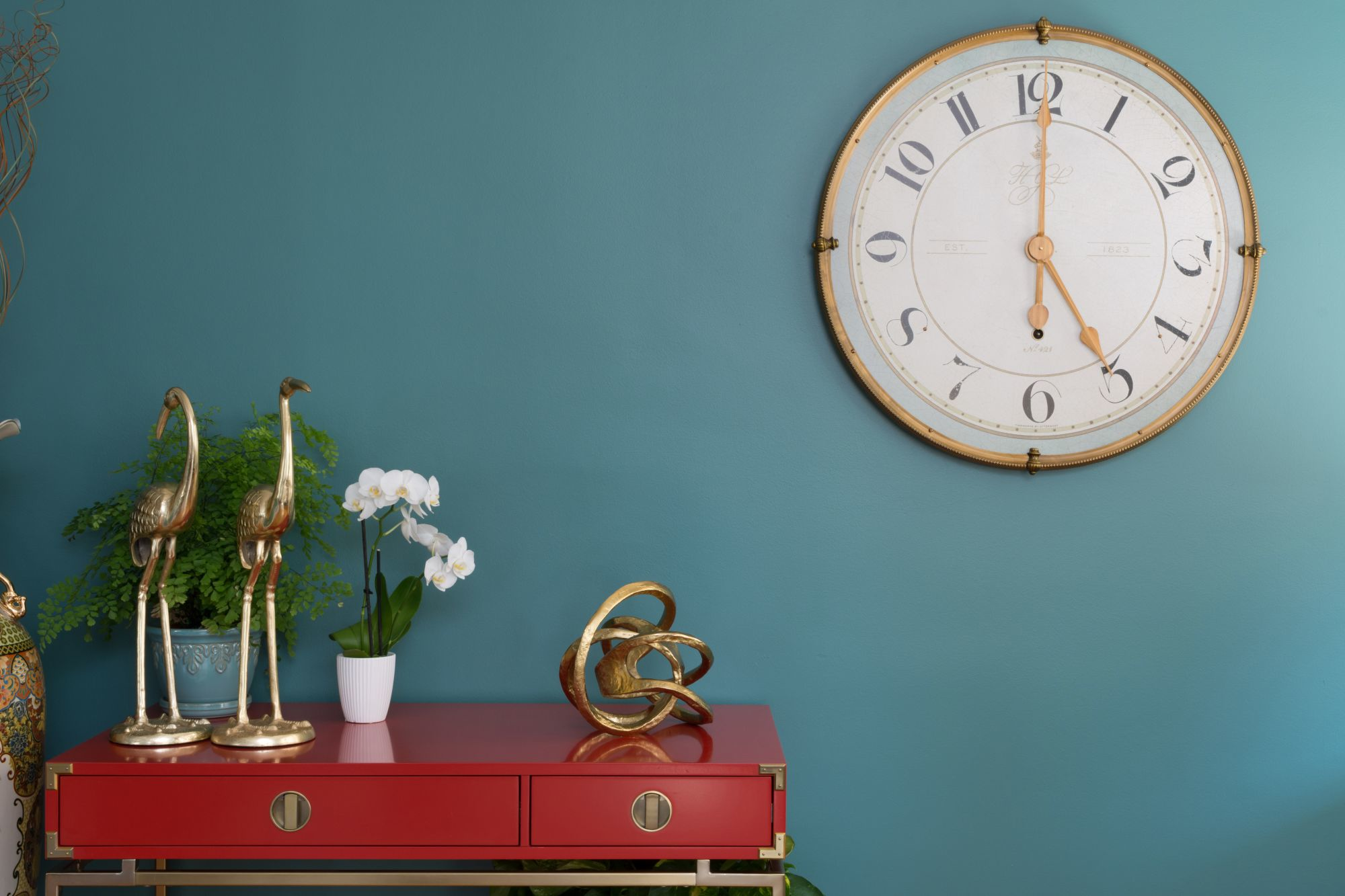 A red console table with gold accessories. The backgrounding wall is painted in The green hour (2018 colour of the year by Dunn Edwards).