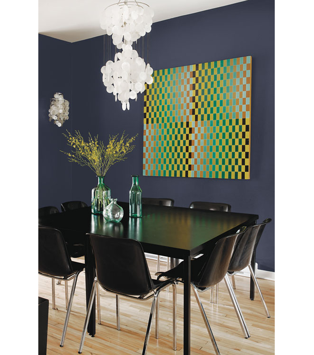 Dining area with black furniture. Back wall painted in Black Flame (2018 colour of the year by PPG paints). The big artwork in the tones of green, yellow and black matches with the vases on the table.