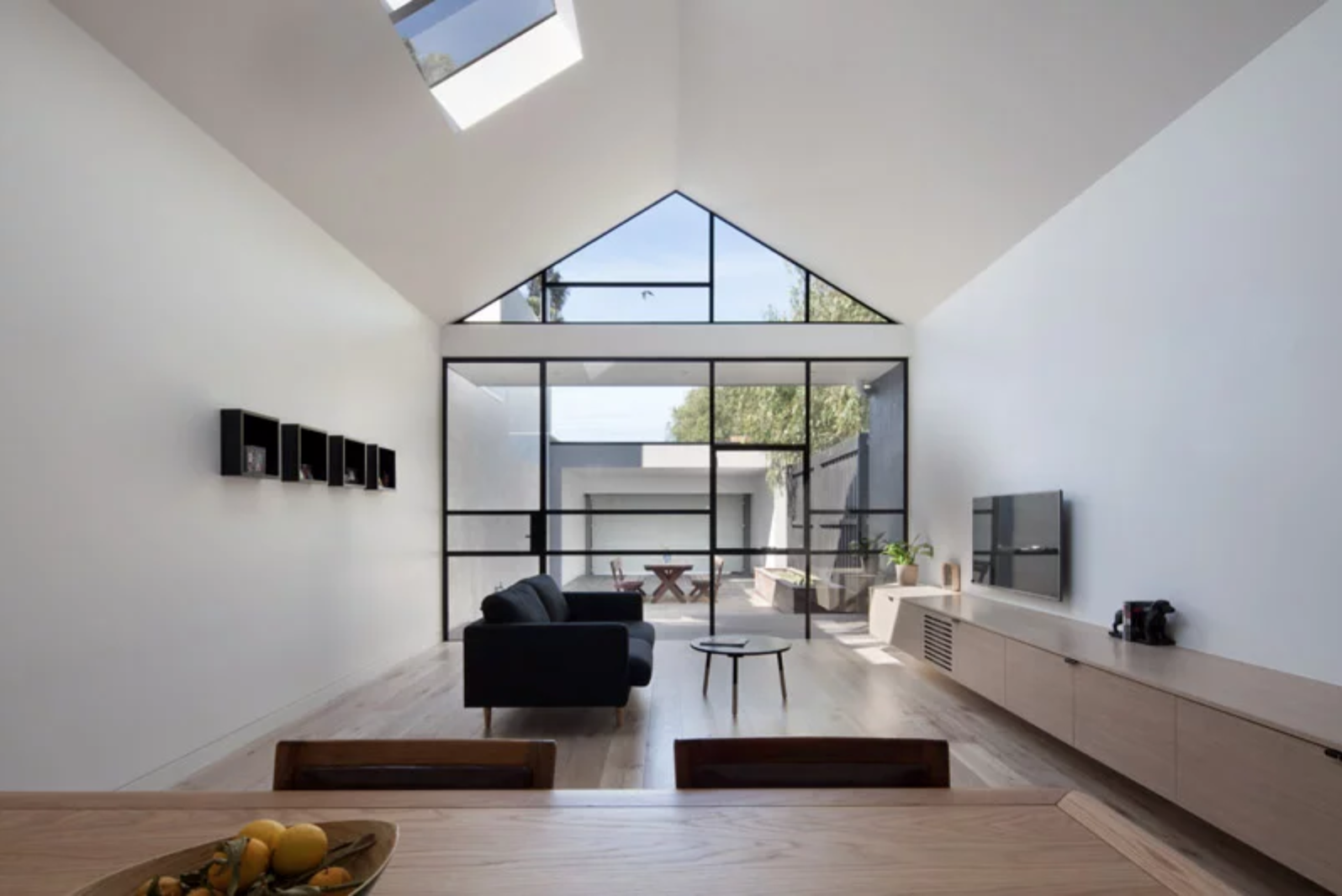 Open plan minimal apartment, with uninterrupted view from the kitchen to the patio, great example of biophilic design.