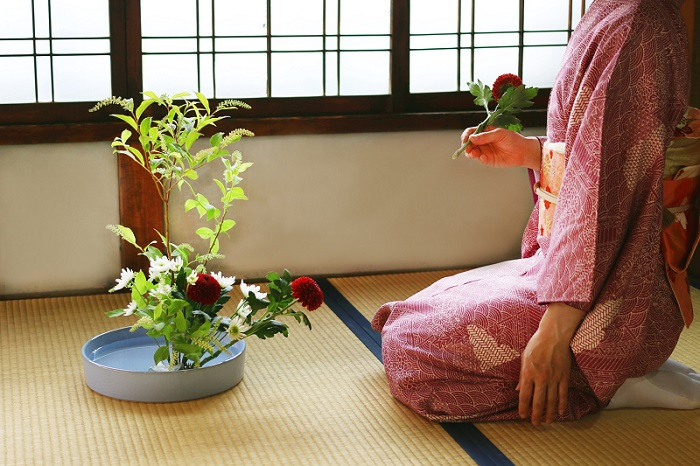 Woman arranging flowers in an Ikebana composition.