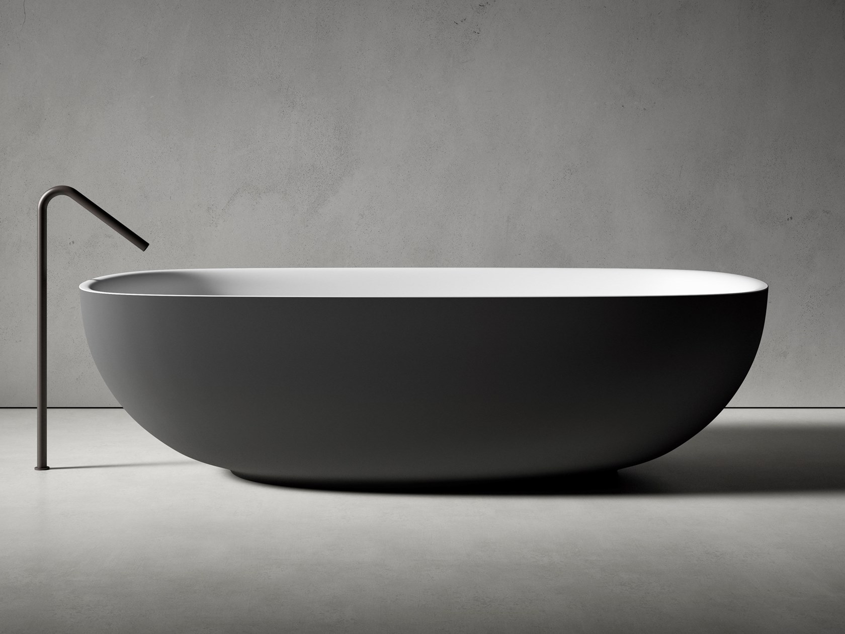 Bathtub with an oval shape and rounded floor-mounted faucet.