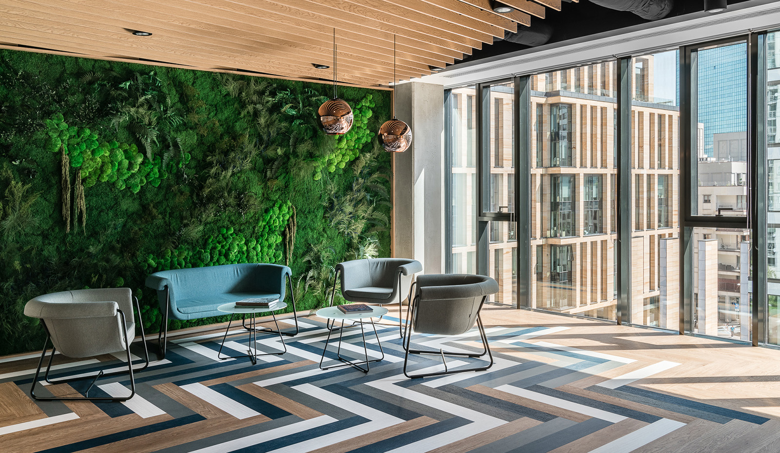 View of a biophilic office sitting area with a vertical garden wall behind it.