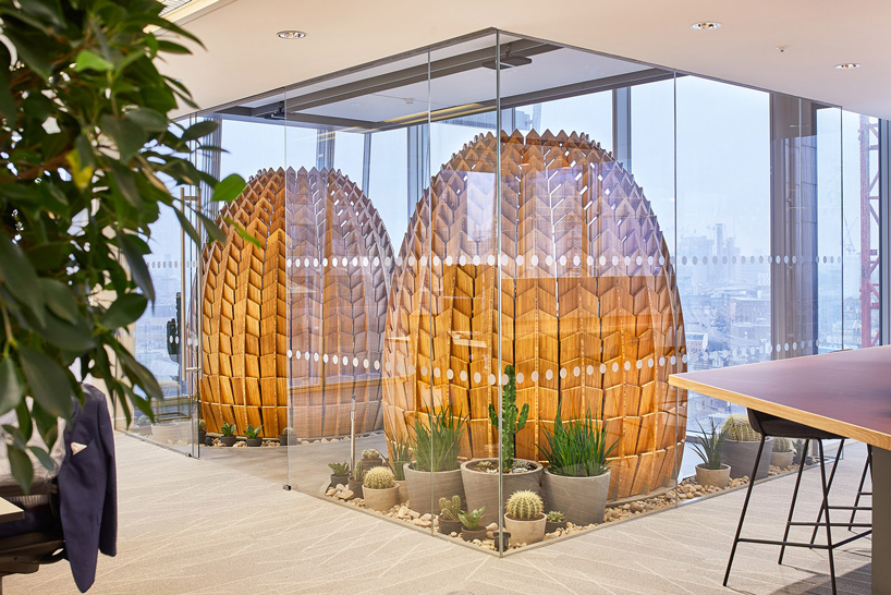 Wooden retreat pods in a biophilic office with a shape that recalls a pinecone.