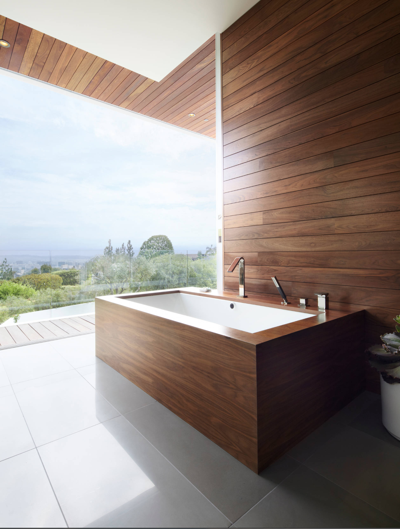 A contemporary bathroom with smooth wood panels on the wall as well as around the bathtub.