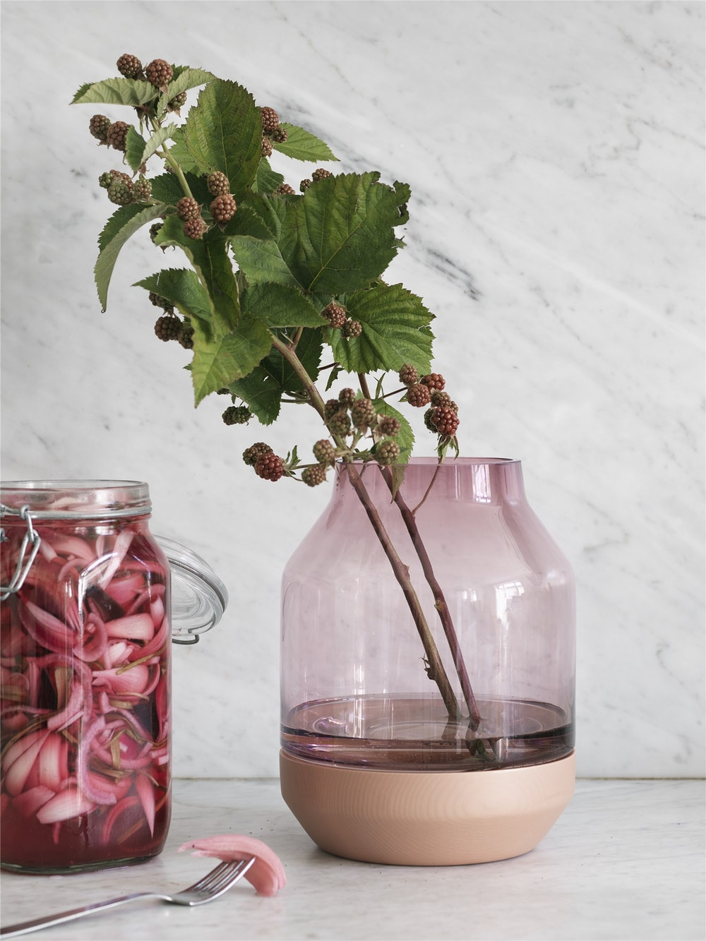 A modern glass vase with wooden bottom.
