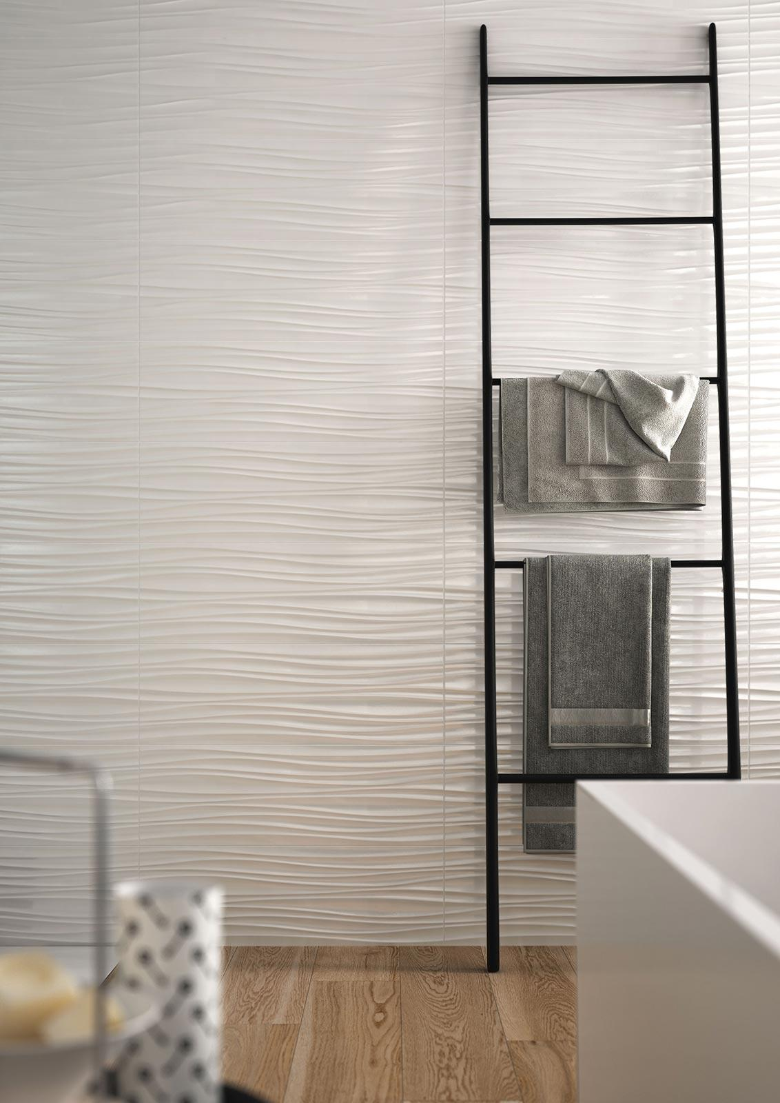 Bathroom wall with textured tiles recalling the wavy shape of sand moved by the wind.