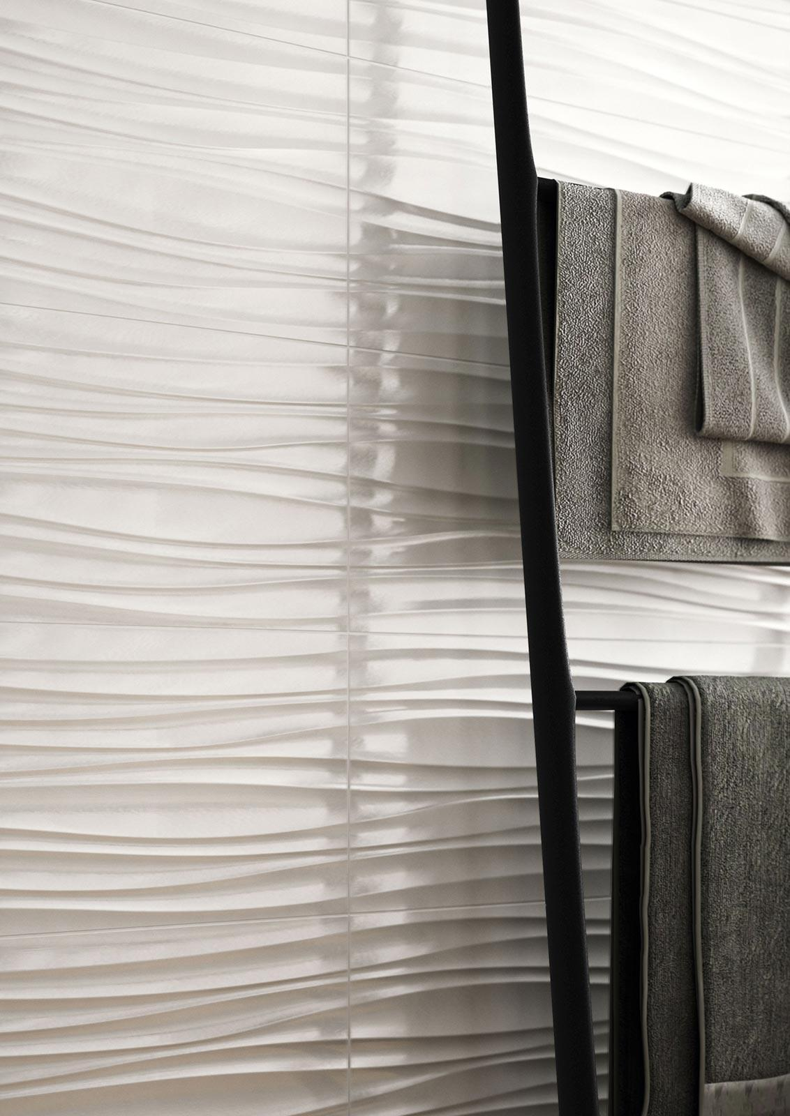 Close-up of textured wall tiles recalling the wavy shape of sand moved by the wind.