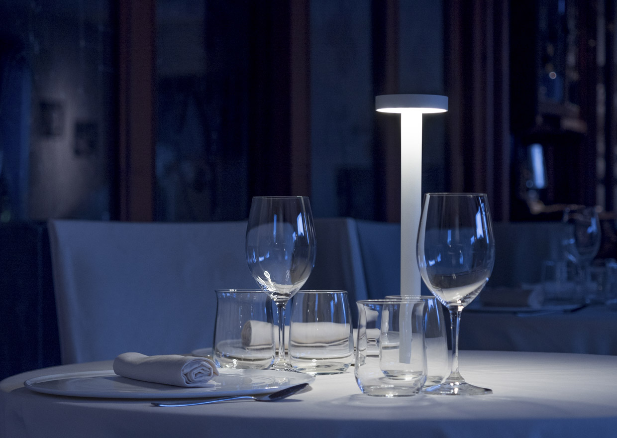 Portable table lamp creating a romantic atmosphere on a dining table.