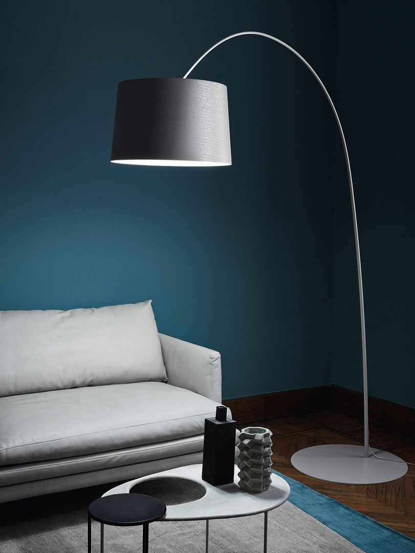 Close-up of a white sofa with a big floor lamp over it.