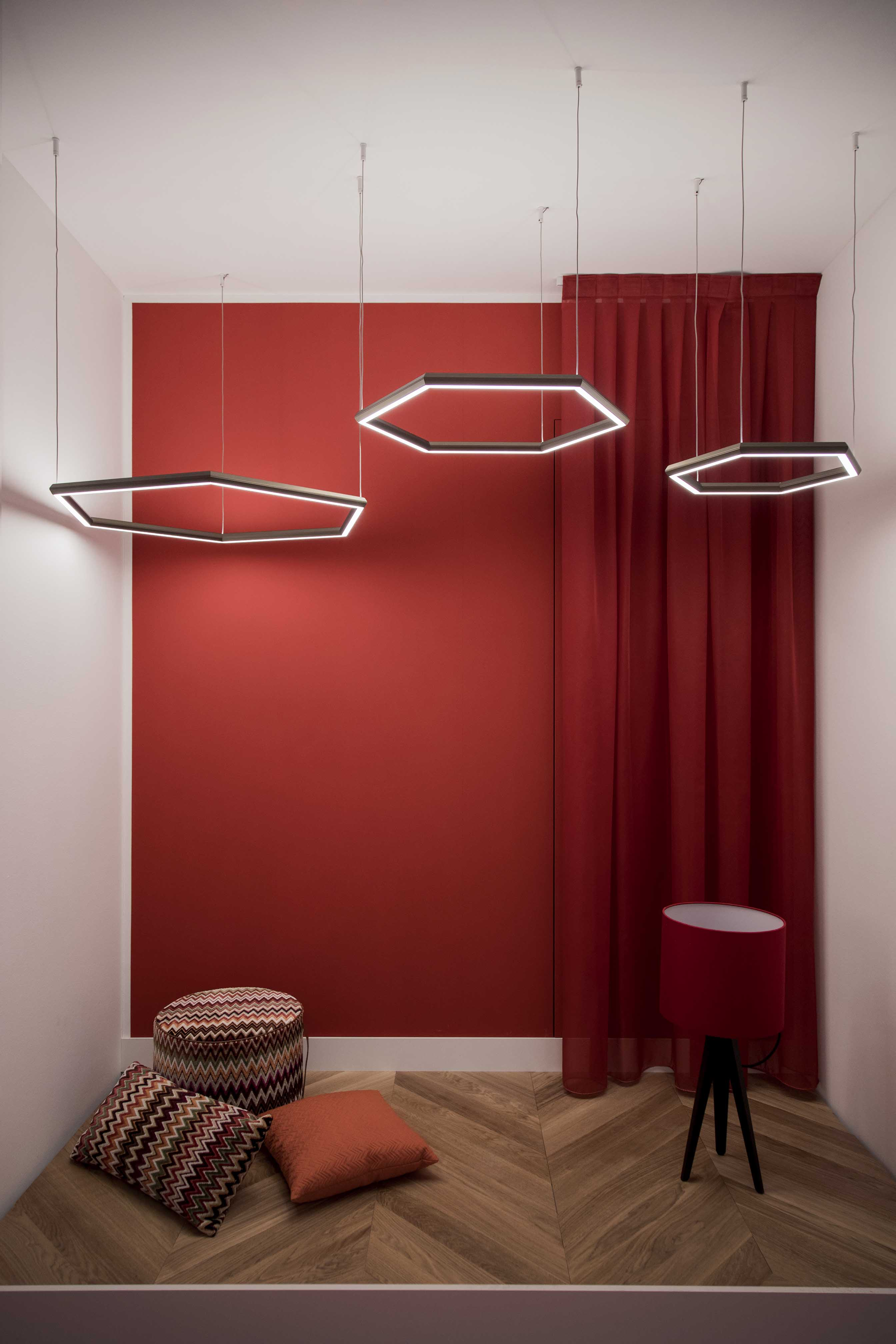Hexagonal pendant lights hanging from the wall in a changing room with a focal back wall painted in red.