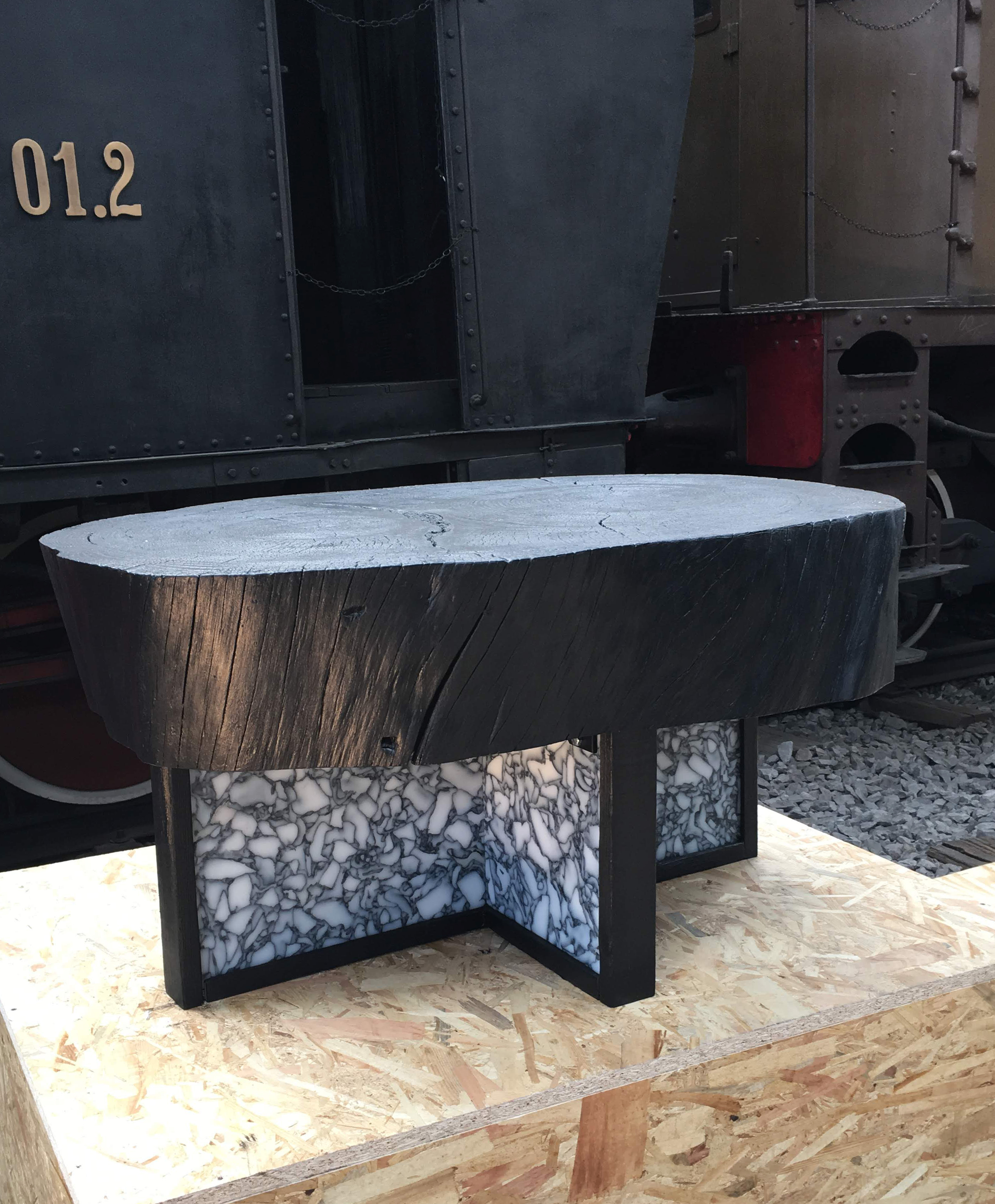 Black coffee table with wooden top and recycled plastic base; one of the plastic recycling design projects joining the Guiltless Plastic Initiative.