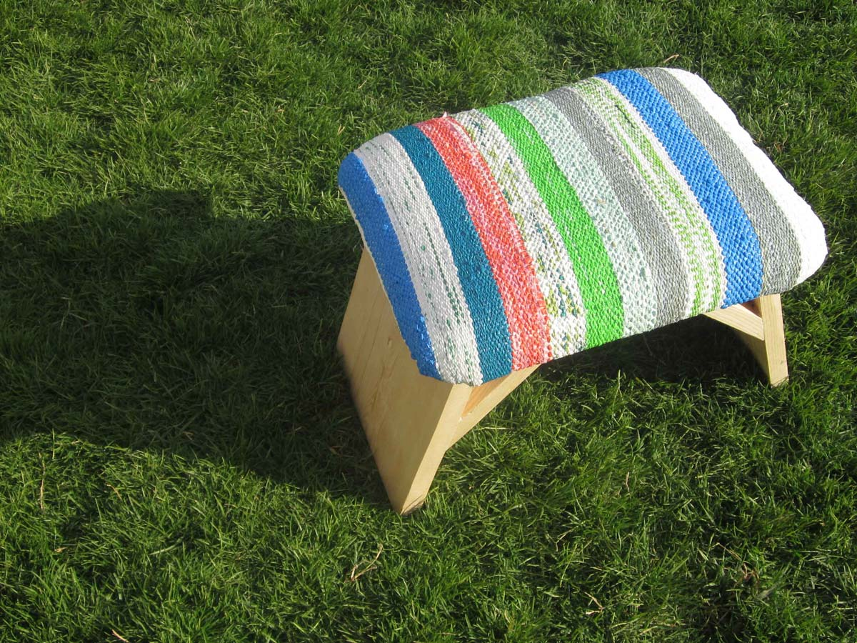 Wooden stool with seat upholstered with Plastex, a sustainable material made recycling plastic bags.