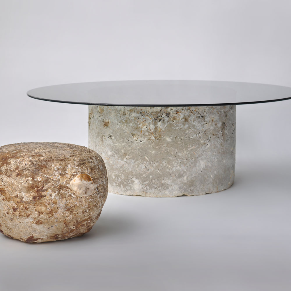 A round table with biofabricated base out of mycelium and glass top.