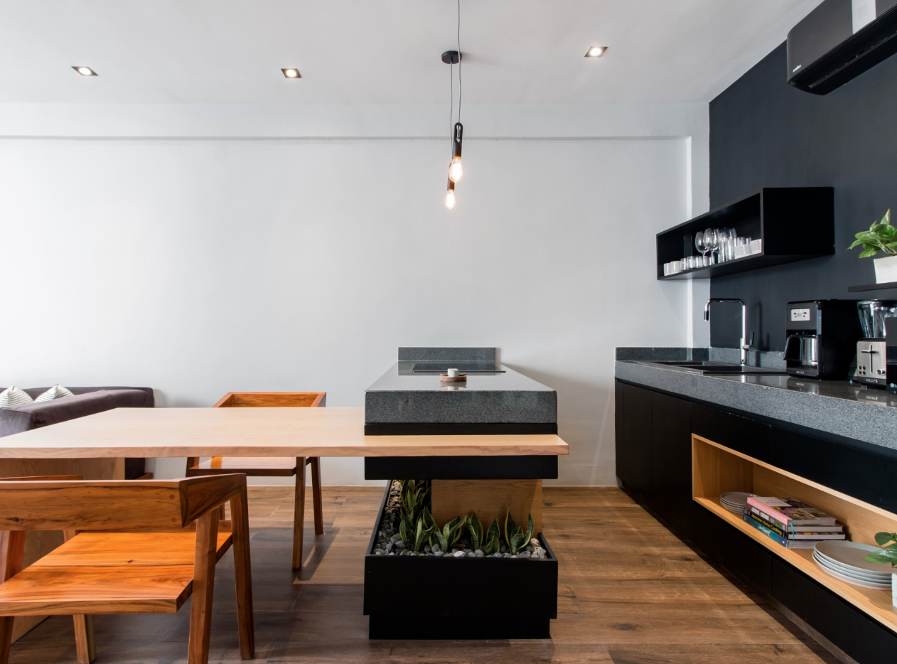 In this minimal apartment, a built-in planter wraps around the kitchen island, creating the perfect spot for plants.