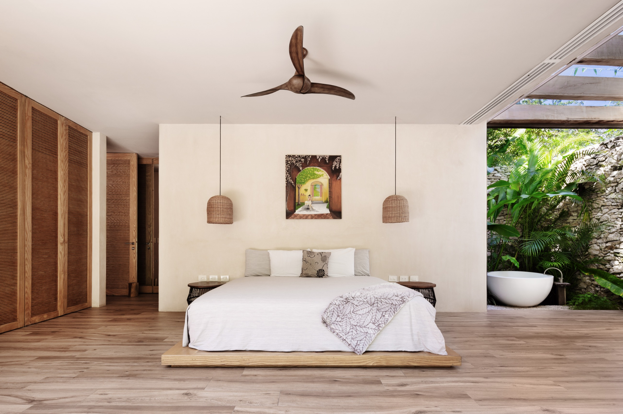 One of the bedrooms of Villa Verde. On the side of the bed is an opening to the outdoors, where a free-standing bathtub is located.