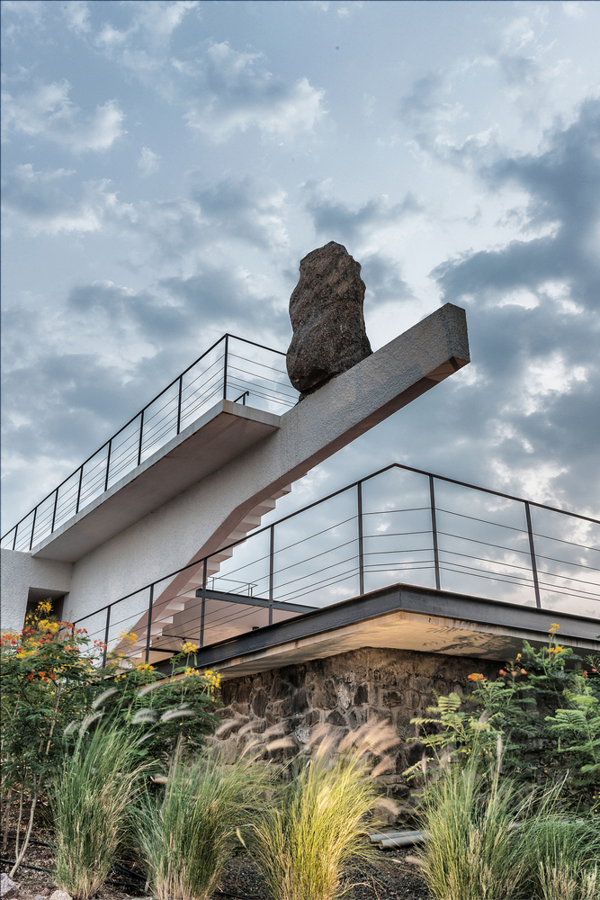 Exterior cantilever pillar feature supporting a huge rock that seems teetering.