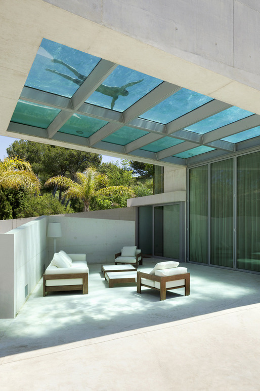 Pool with a glass bottom located over a seating area.