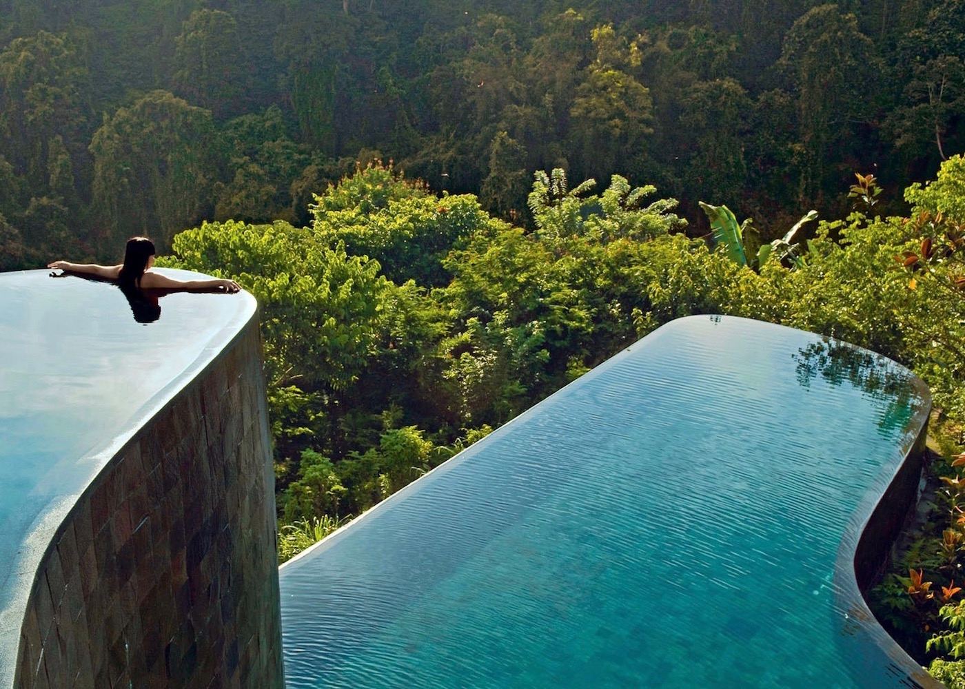 A terraced infinity pool that seems to go right into the forest with a woman on the edge.