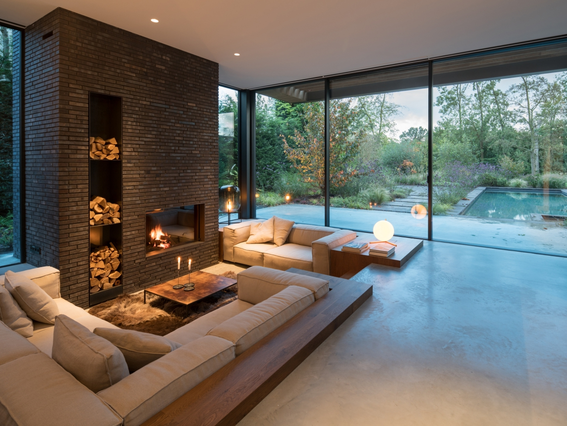 Biophilic living room with big windows leaving the view to the outside totally open.