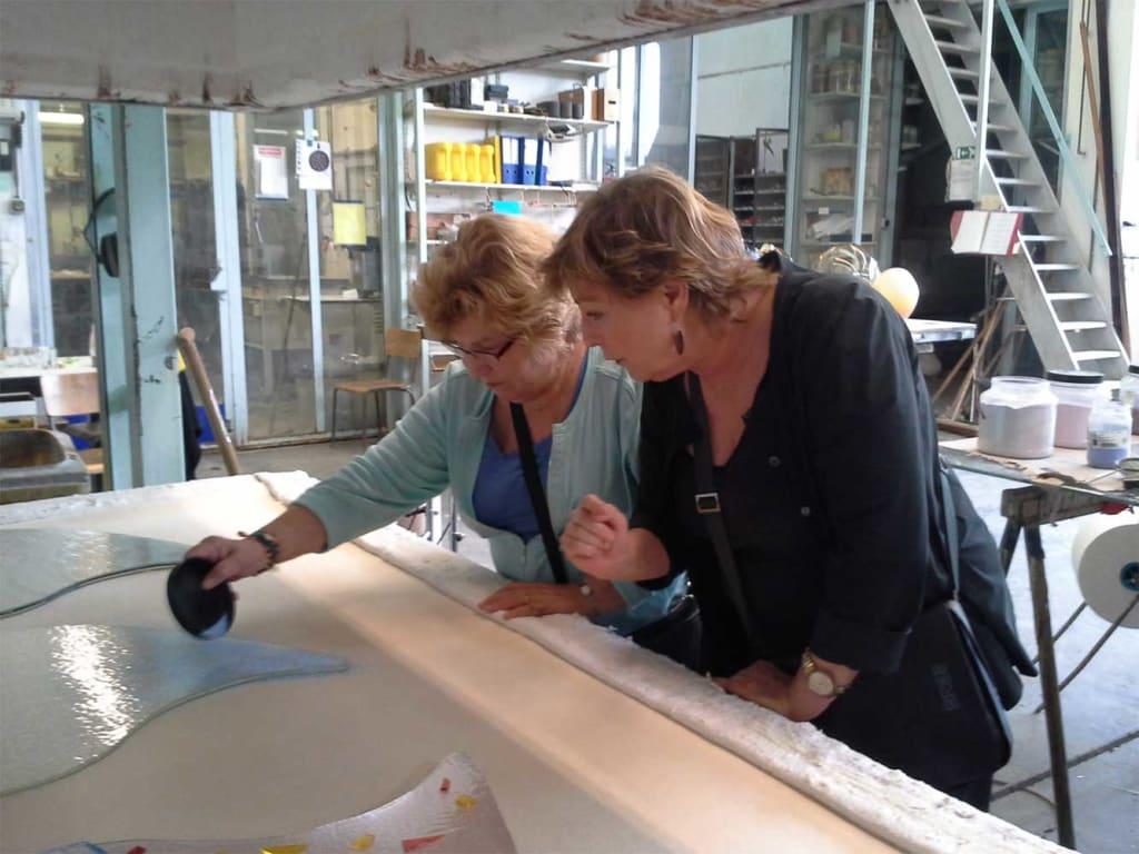 Werk aan kleurrijk grafmonument van glas met harten voor partner en ouder