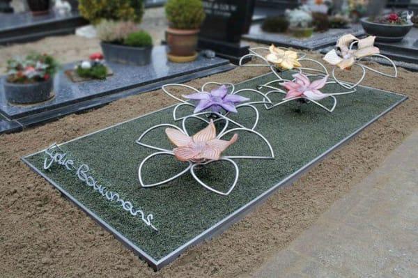 Artistiek RVS grafmonument met glazen bloemen voor jonge vrouw en naam in eigen handschrift