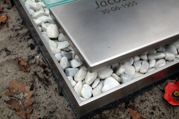 detail van RVS graf met witte stenen