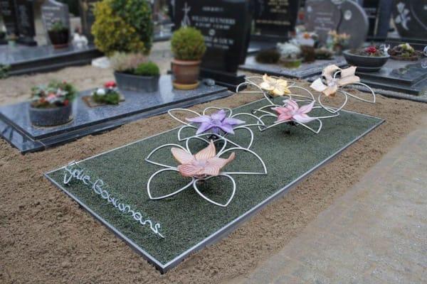 Modern RVS grafmonument met glazen bloemen voor jonge vrouw en naam in eigen handschrift