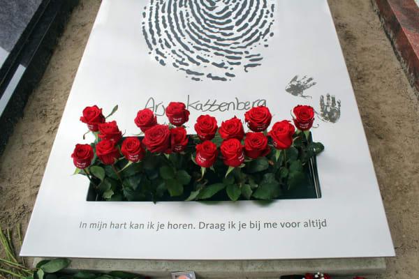 bloemen op eigentijds rvs grafmonument
