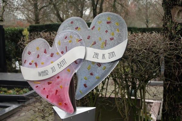 Samengesmolten glazen harten op RVS grafmonument voor partner en vader