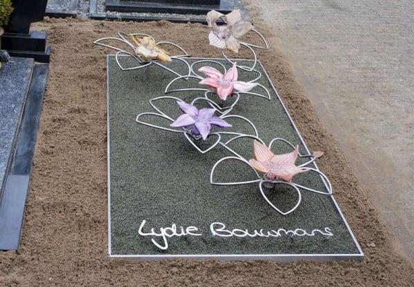 Eigentijds RVS grafmonument met glazen bloemen voor jonge vrouw
