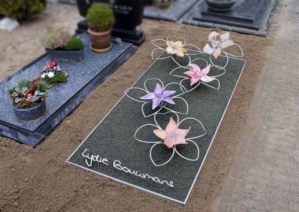 Eigentijds en abstract grafmonument met RVS en glazen bloemen voor jonge vrouw en naam in eigen handschrift