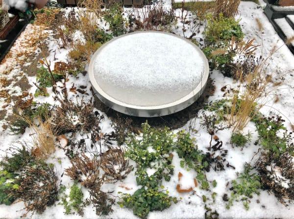 Kunstzinnige Grafzerk met ronde RVS spiegel in de sneeuw