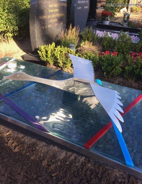 Eigentijds grafmonument van glas met RVS zwaan en handafdrukken voor partner