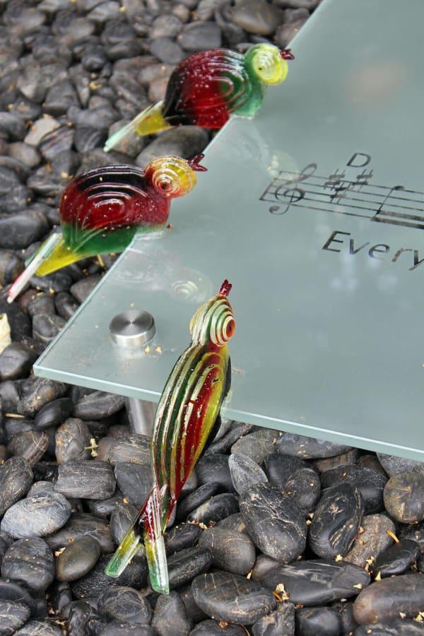 grafsteen van glas met vogels detail