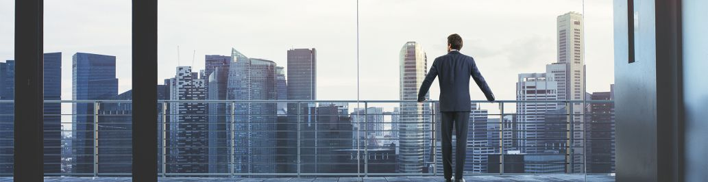 A businessman is standing on a balcony at his office while looking at the city.