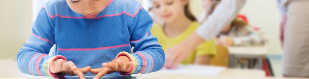 A child is using a tablet in his early childhood education class.