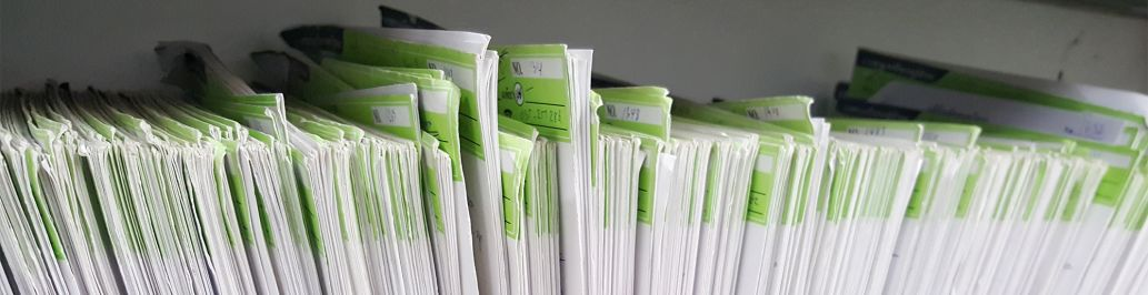 A healthcare administration office has paperwork sitting on a shelf.