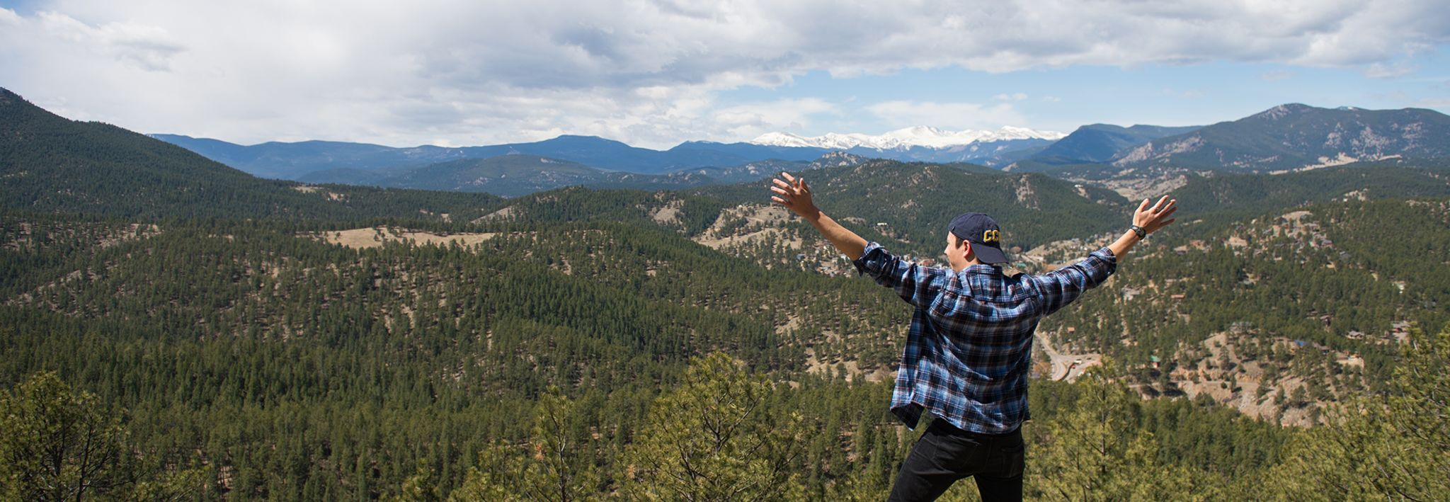 A CCU student is posing in the mountains of Colorado.