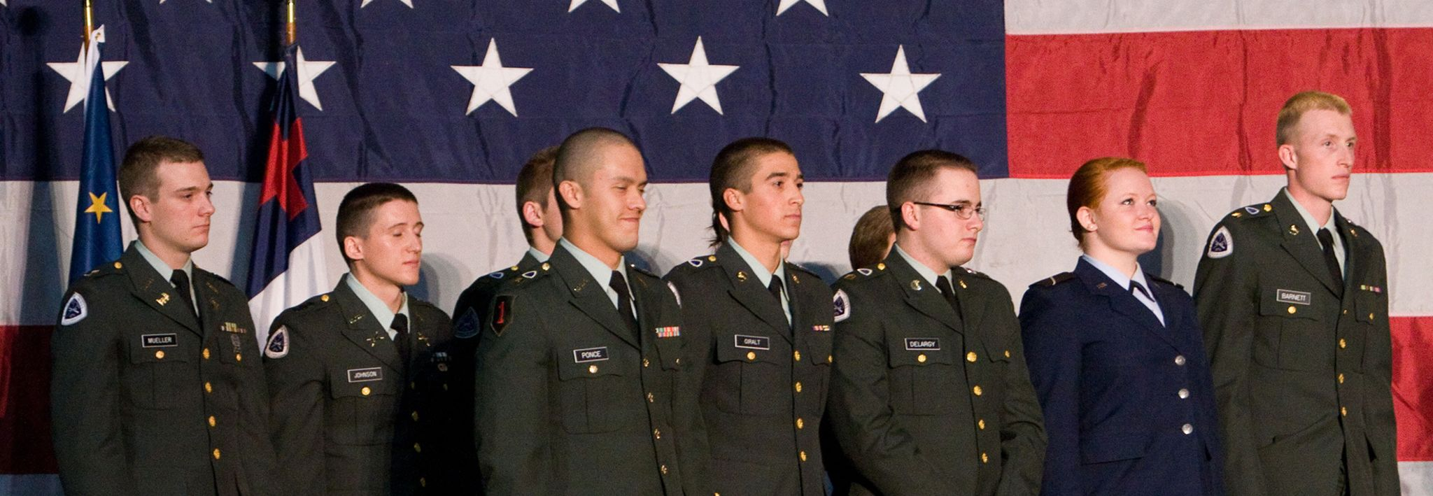Colorado Christian University students involved in ROTC pose for a photo in front of an American flag.