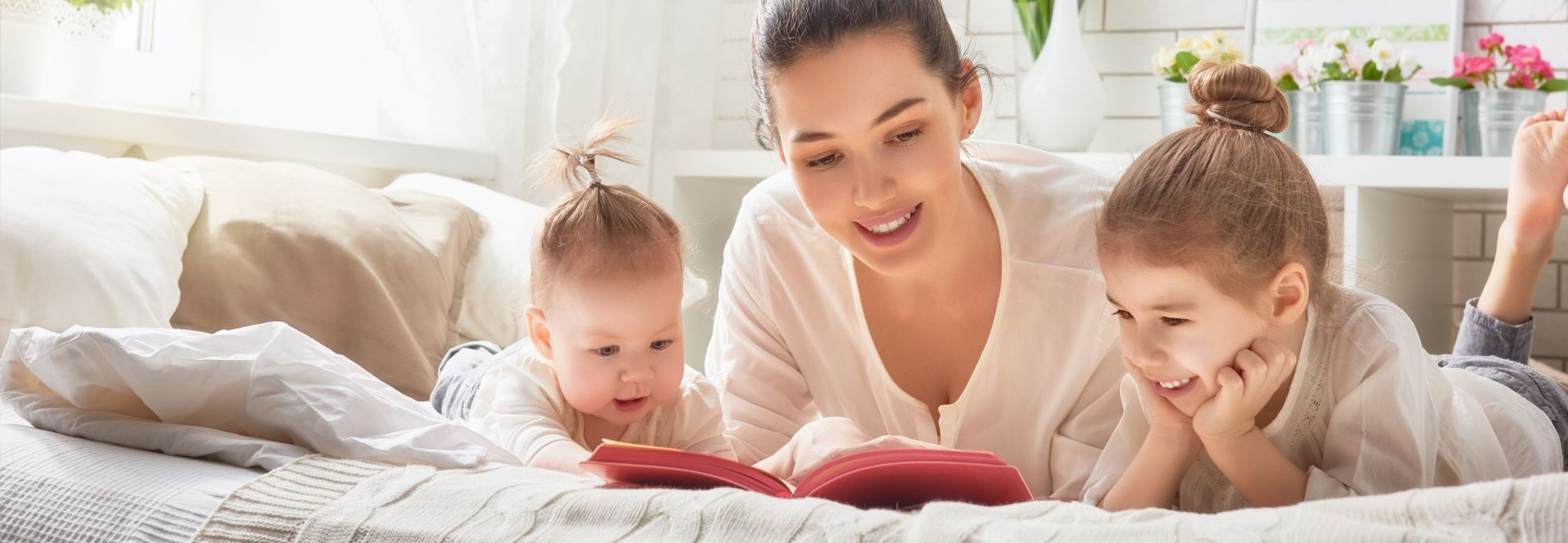 A young mother is reading a book to her two daughters.