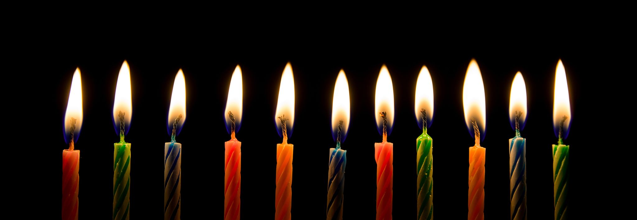 Eleven birthday candles are lit on a birthday cake.
