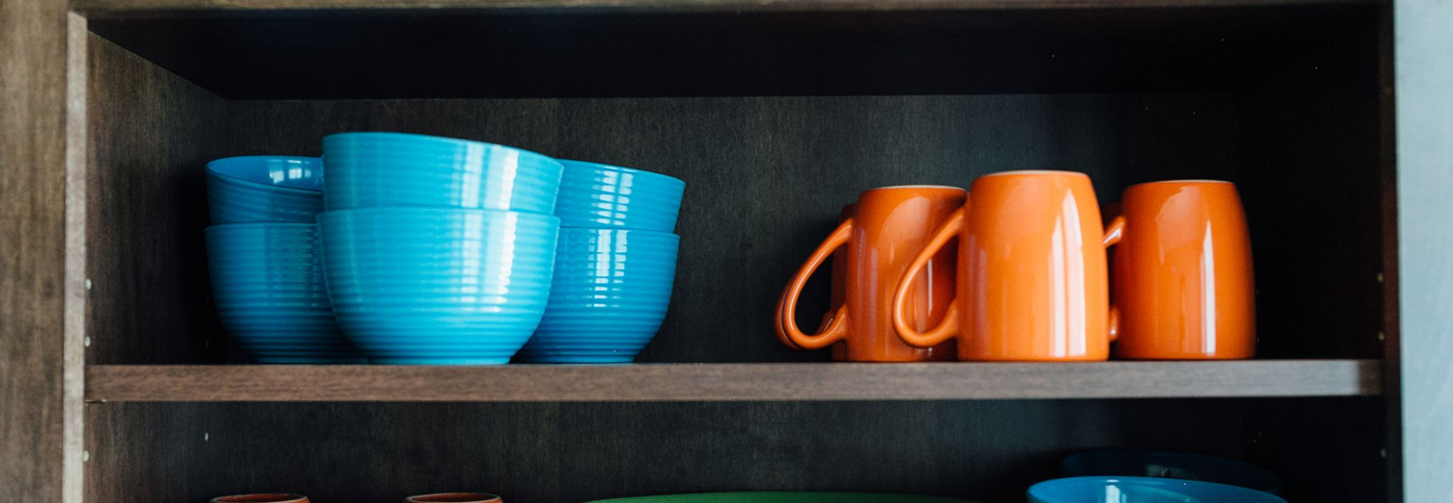 Blue dishes and orange cups are sitting on a shelf in the kitchen.