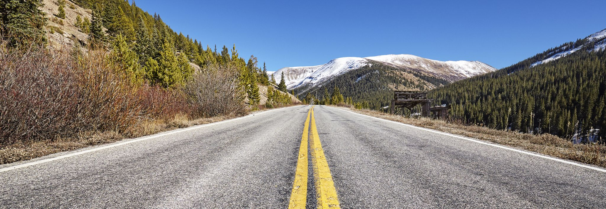 A road in the mountains leads to a snowy peak in Colorado.