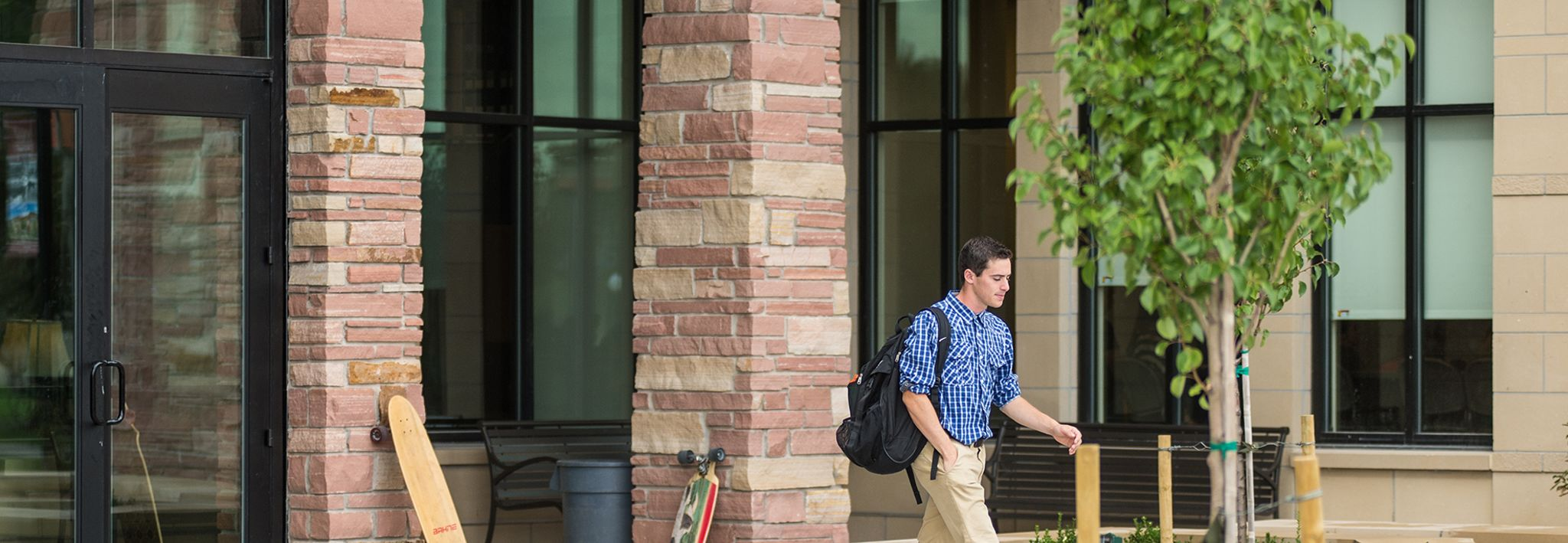 A male student is walking outside of Leprino Hall at CCU.